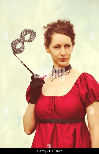 eine Frau in einem roten Kleid Periode und eine venezianische Maske Stockbild
