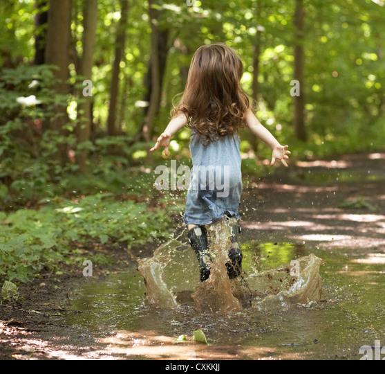 Kleines Mädchen in Pfütze springen Stockbild