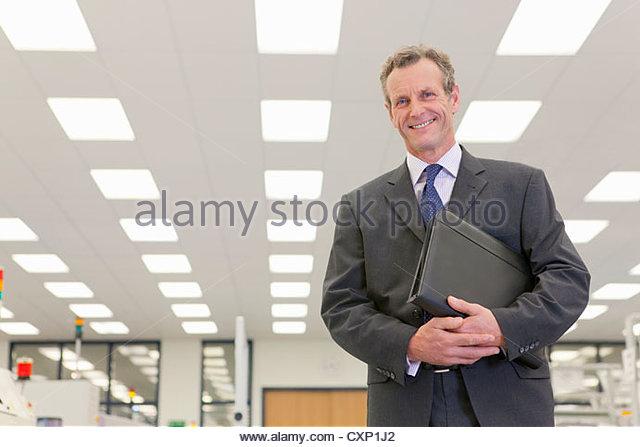 Porträt von lächelnden Geschäftsmann in Hightech-Elektronik-Fabrik Stockbild