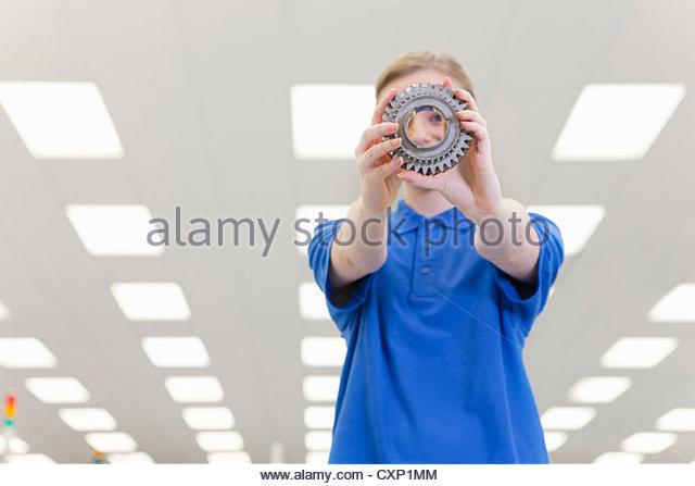 Porträt von lächelnden Ingenieur spähte durch Zahnrad Stockbild