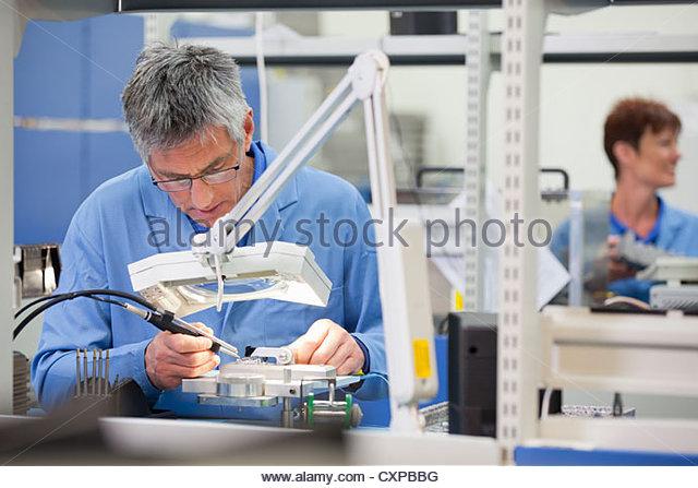 Techniker arbeiten am Fließband in Hi-Tech-Gerätewerk Stockbild