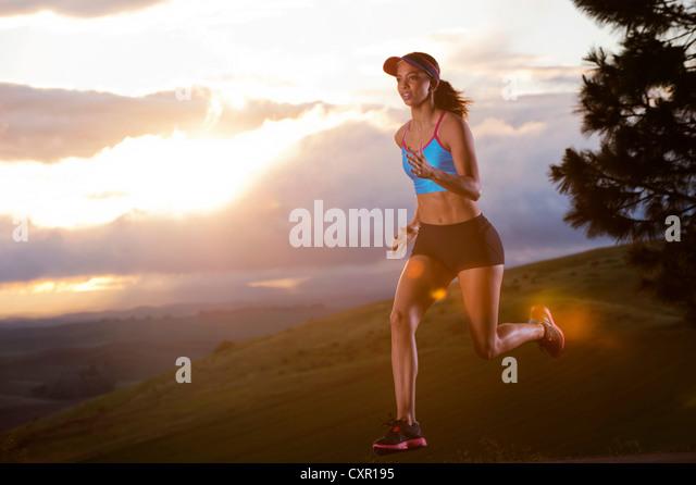 Junge Frau läuft in ländlicher Umgebung bei Sonnenaufgang Stockbild