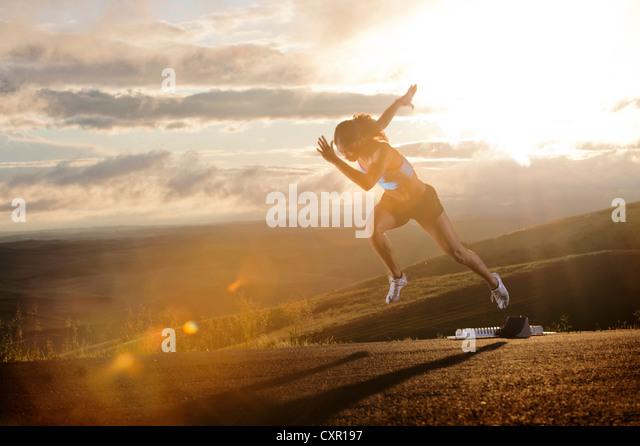 Junge Frau Anfahren Startblöcken in ländlicher Umgebung Stockbild