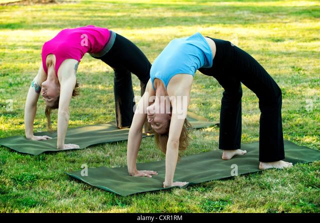 Zwei Frauen bücken nach hinten auf Yoga-Matten im freien Stockbild
