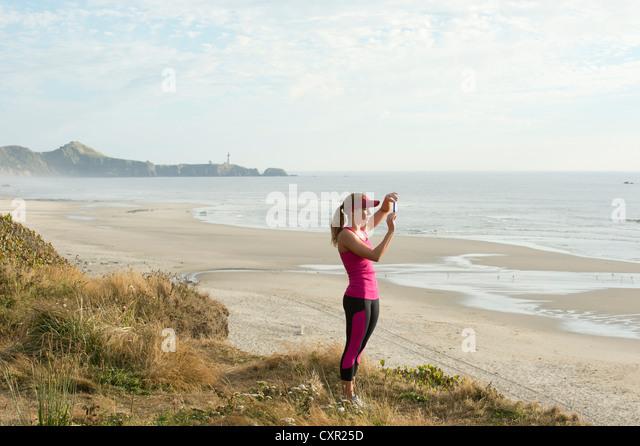 Aktive junge Frau nehmen Foto am Strand Stockbild