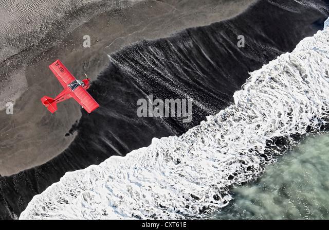 Luftaufnahme, eine rote einmotorigen leichten Flugzeug fliegen über die Wellen des Nordatlantiks, schwarze Stockbild