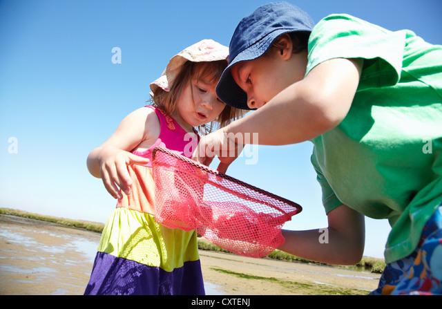 Kinder untersuchen Fischernetze Stockbild