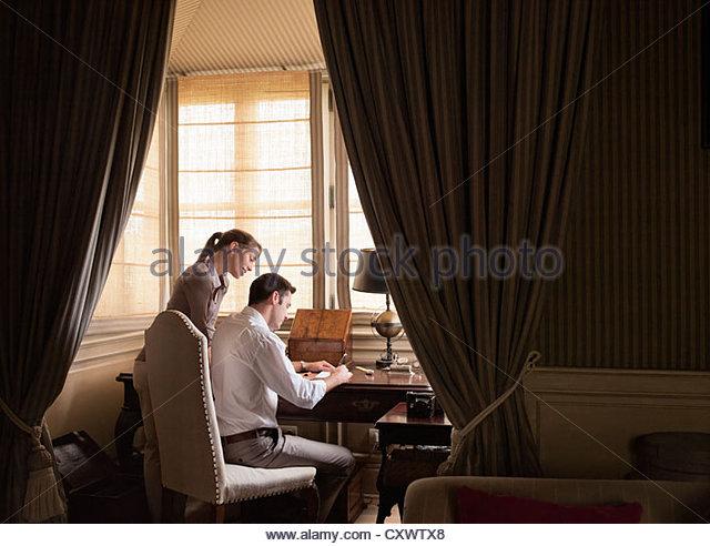 Paar schreiben am Schreibtisch in Studie Stockbild