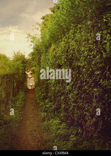Eine Frau in einem weißen Kleid floral, zu Fuß entlang eines Pfades in einem Garten / Labyrinth. Stockbild