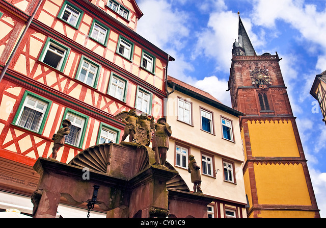 Wertheim, Franken, Deutschland, eine mittelalterliche Wasser gut vor Kreuz Fachwerkhäuser und ein Clock tower Stockbild