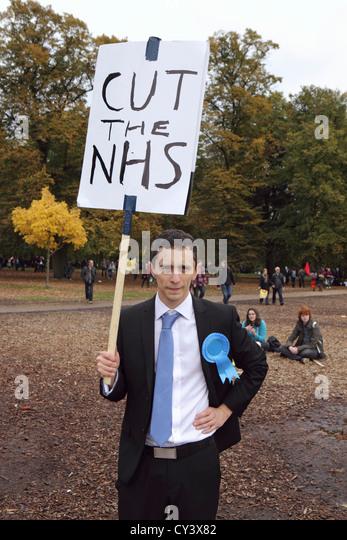 """Anti-Regierung schneidet Demonstrant in A Future, die Works, London. Mit Plakat """"Schnitt des NHS"""", London Stockbild"""