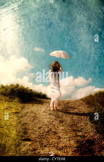 eine Mädchen in einem weißen Kleid ist Fuß in den Dünen mit einem Sonnenschirm Stockbild
