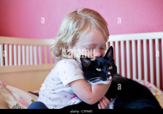 Kleinkind Mädchen umarmt ihre Katze. Stockbild