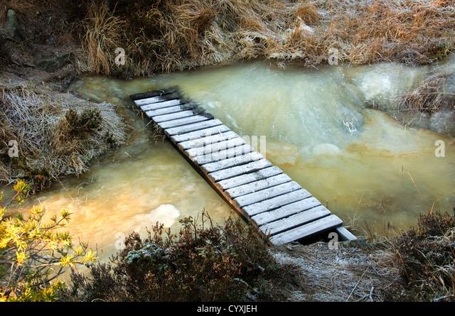 Eine Holzbrücke über einen eisigen Strom Stockbild