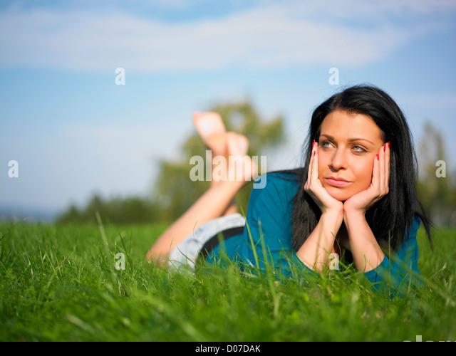 Entspannende junge Frau im Park auf dem grünen Rasen Stockbild