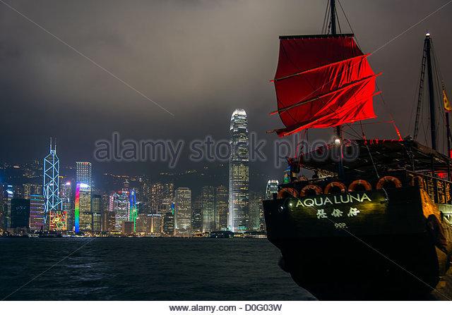 Rote Segel-Dschunke mit Nacht Skyline im Hintergrund, Hong Kong, China Stockbild