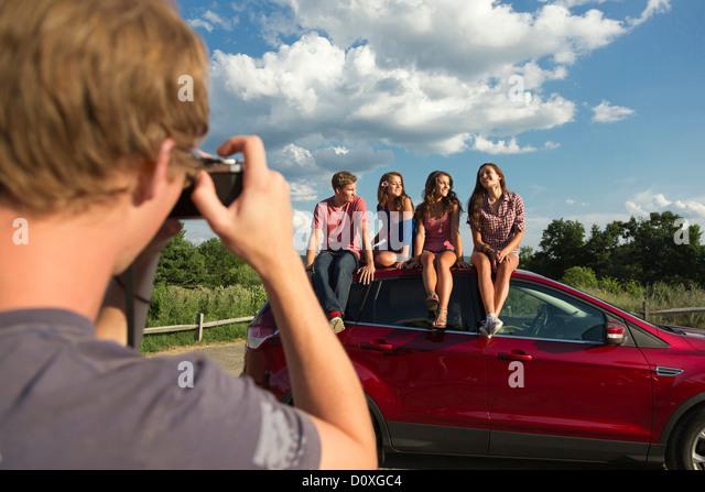 Freunde sitzen auf Autodach, jungen Mann Fotografieren Stockbild