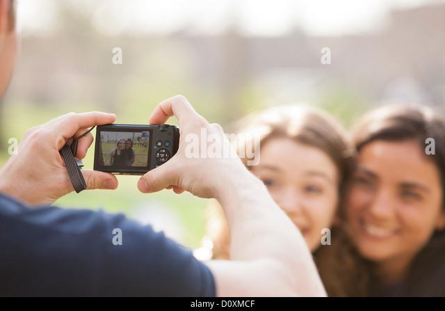 Mann mit dem Fotografieren von zwei jungen Frauen Stockbild