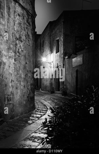 Gebogene Kopfsteinpflasterstraße zwischen Gebäuden in Sizilien von Straßenlaternen beleuchtet Stockbild