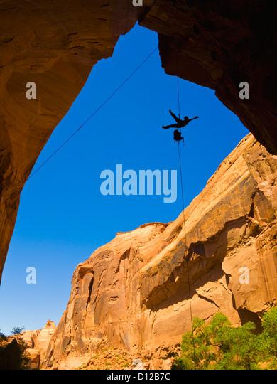 Eine Sportlerin Rappeling eine trockene Utah Slotcanyon Wasserfall hinunter; Hanksville Utah Vereinigte Staaten Stockbild