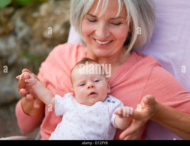 Deutschland, Bayern, Frau mit Enkelkind sitzt in Liegestuhl, Lächeln Stockbild