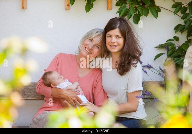 Deutschland, Bayern, drei Generationen zusammen zu sitzen, Lächeln Stockbild
