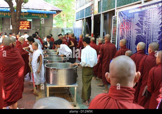 Buddhistische Mönche versammeln sich für eine gemeinsame Mahlzeit in der Mahagandhahon Abtei (Amarapura Stockbild