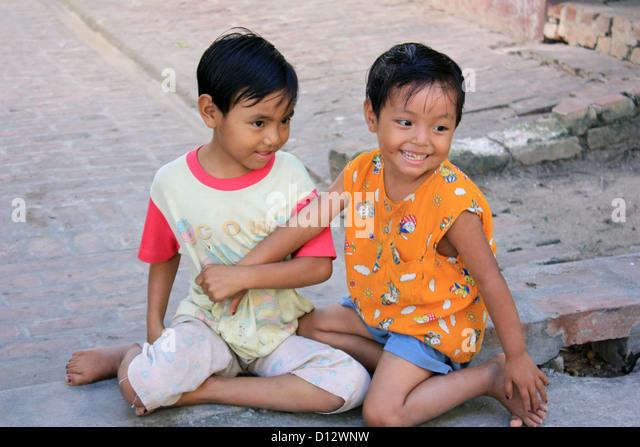 Zwei kleine Mädchen spielen auf der Straße in Mandalay (Amarapura Township), Myanmar, 25. Oktober 2012. Stockbild