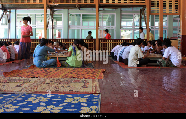 Menschen sitzen zusammen zum Mittagessen in der Mahagandhahon Abtei in Mandalay (Amarapura Township), Myanmar, 25. Stockbild