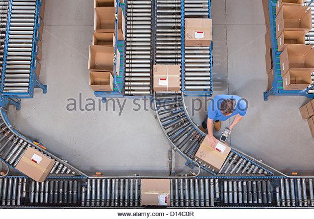 Arbeiter mit Barcode-Reader Scannen Box auf Förderband im Auslieferungslager Stockbild