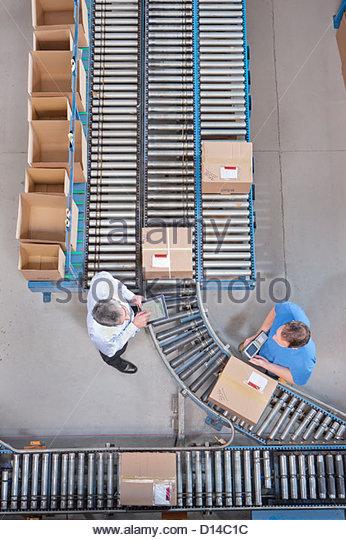 Geschäftsmann mit digital-Tablette und Arbeitskraft Verpackung am Förderband im Auslieferungslager Stockbild