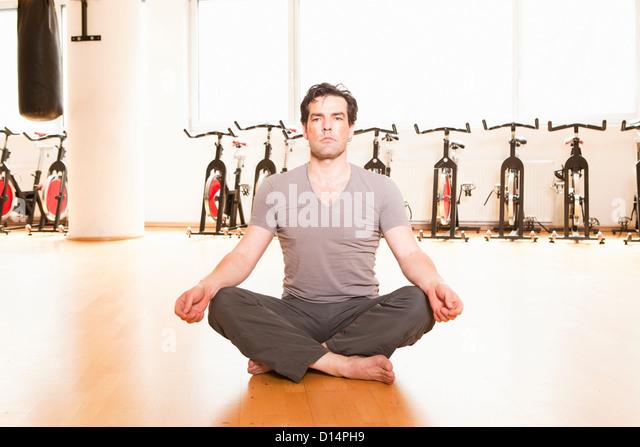 Menschen, die meditieren auf Matte zu Fitness-Studio Stockbild