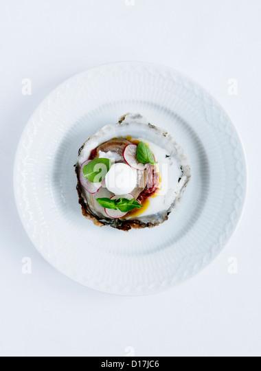 Teller mit Austern mit Radieschen und Kräutern Stockbild