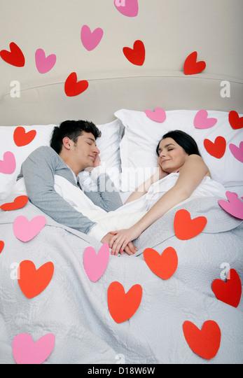 Paar im Bett mit Herzformen auf Bettwäsche Stockbild
