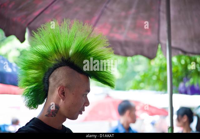 Thai Mann mit grünen Haaren und eine Tätowierung auf dem Sonntagsmarkt Stockbild