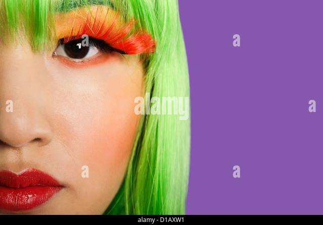 Zugeschnittenes Bild junge Frau trägt falsche Wimpern lila Hintergrund Stockbild