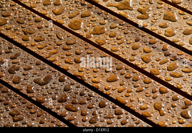 Regentropfen auf Teakholz Stockbild