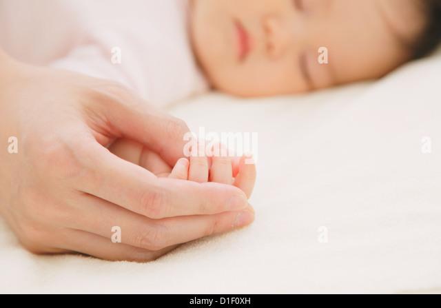 Babyjungen schlafen im Bett und seine Mutter Hand in Hand Stockbild