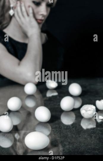 eine Frau sitzt an einem Tisch vor mehrere Eizellen, einige von ihnen gebrochen Stockbild