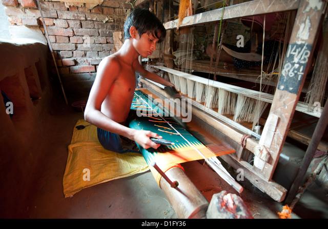 Kleiner Junge am Webstuhl weben gemusterte Seide Sari mit mehreren Spulen von Seide, Vaidyanathpur weben Dorf, Orissa, Stockbild