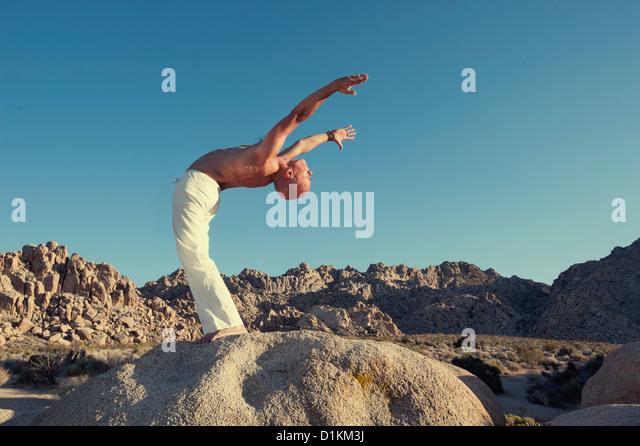 Mann in Yoga-Haltung im Freien im Wald. Stockbild