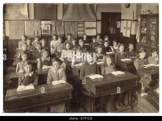 Schule-Foto von junior Mädchen sitzen an ihrem Schreibtisch, mit offenen Bücher im Klassenzimmer - 1930, Stockbild