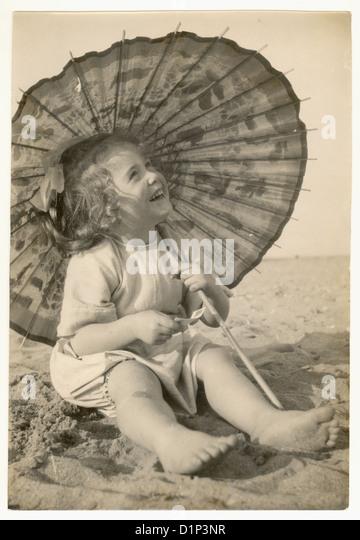 Foto von niedlichen junges Mädchen an einem Strand mit Sonnenschirm, 1930er Jahre Stockbild