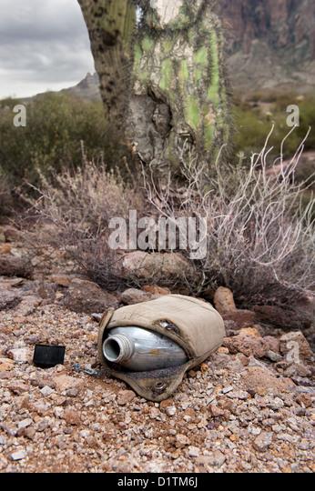 Ein altes liegt Vintage Wandern Kantine in einer verdorrten, trockene Wüste, leer. Stockbild