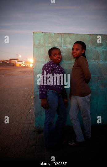 Kinder vor einer Wand in Guguletu Township am Abend, Cape Flats, Cape Town, Südafrika, Afrika Stockbild