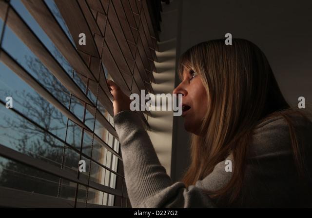 Ängstlich Reife Frau spähte durch Fenster-Vorhänge in der Nacht. Stockbild