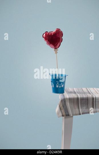 eine herzförmige Ballons auf die Tischkante ausgeglichen Stockbild