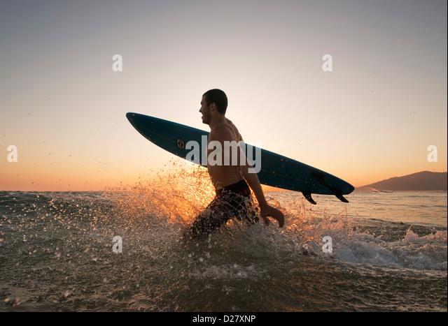 Surfer, die ins Meer laufen. Stockbild