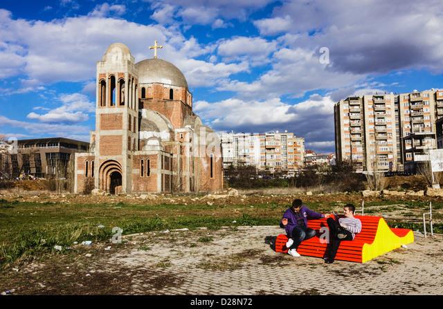 Studenten sitzen auf einer Bank in Pristina Campus durch die unvollendete serbischen orthodoxen Tempel von Heilige Stockbild