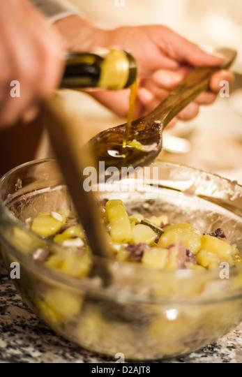 Man gießt Olivenöl in Salat Stockbild